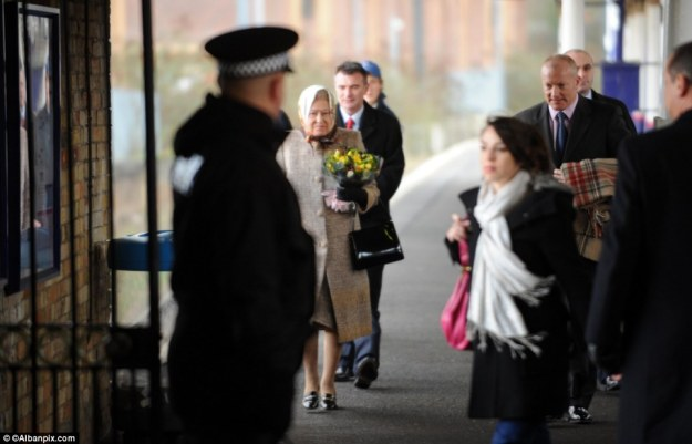 Face in the crowd: A police officer waits for the Queen as she gets off the train at Kings Lynn. She travelled with the minimum of protection