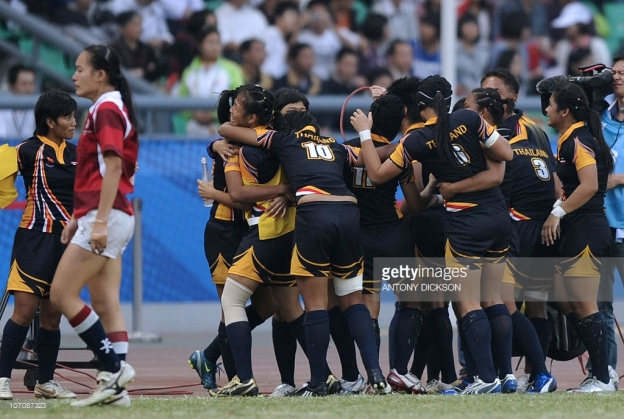A defeated Hong Kong player (L) walks past celebrating Thailand players