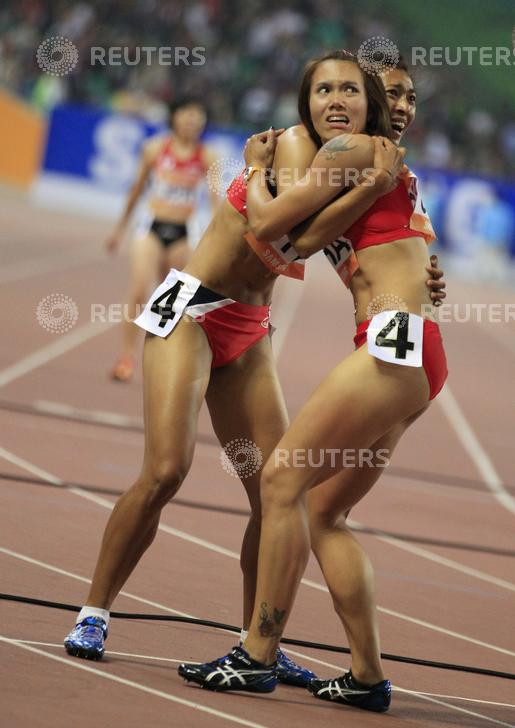 Members of Thailand's women's 4x100m relay team celebrate as their team mate crosses the finish line to win the race at the 16th Asian Games in Guangzhou