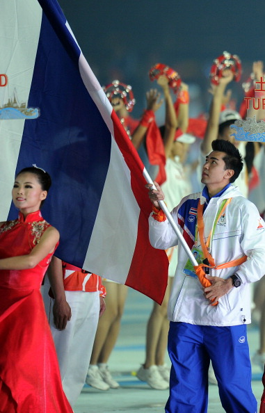 Caption:An athlete from Thailand carries the national flag
