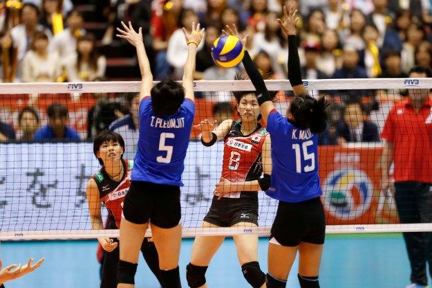 Koga #8 of Japan spikes against Thailand